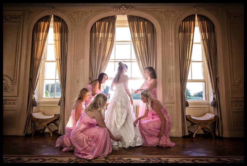 Beautiful photo of bridesmaids adjusting bride's dress at Addington Palace by Peter Denness.jpg