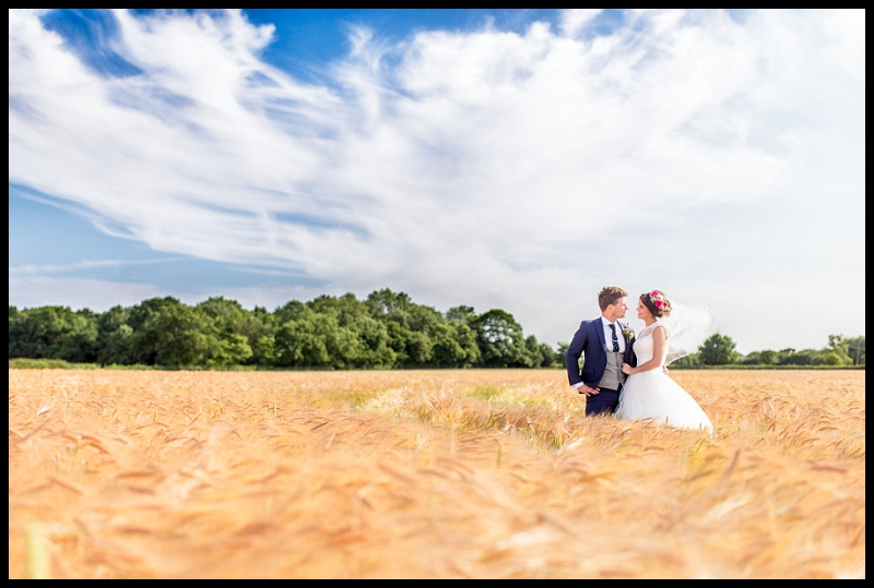 bride and groom in corn field at granary barn