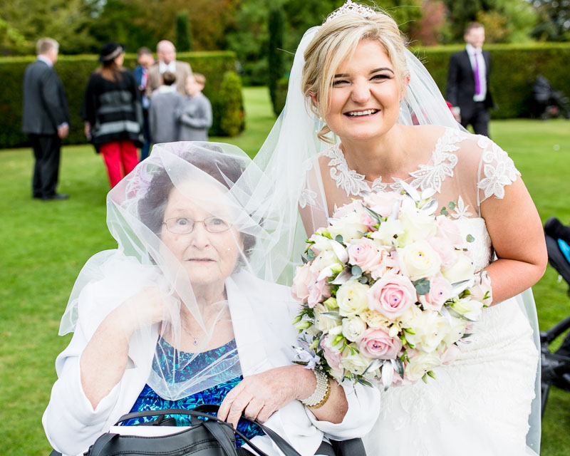 fun photo of bride and her gran with the veil on gran's head