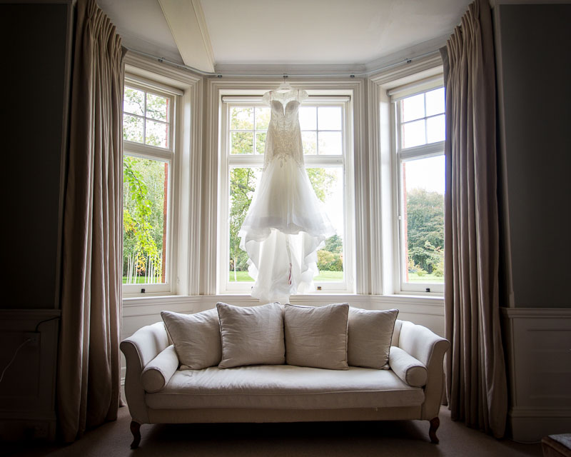 Wedding dress hanging in a window in the bridal suite