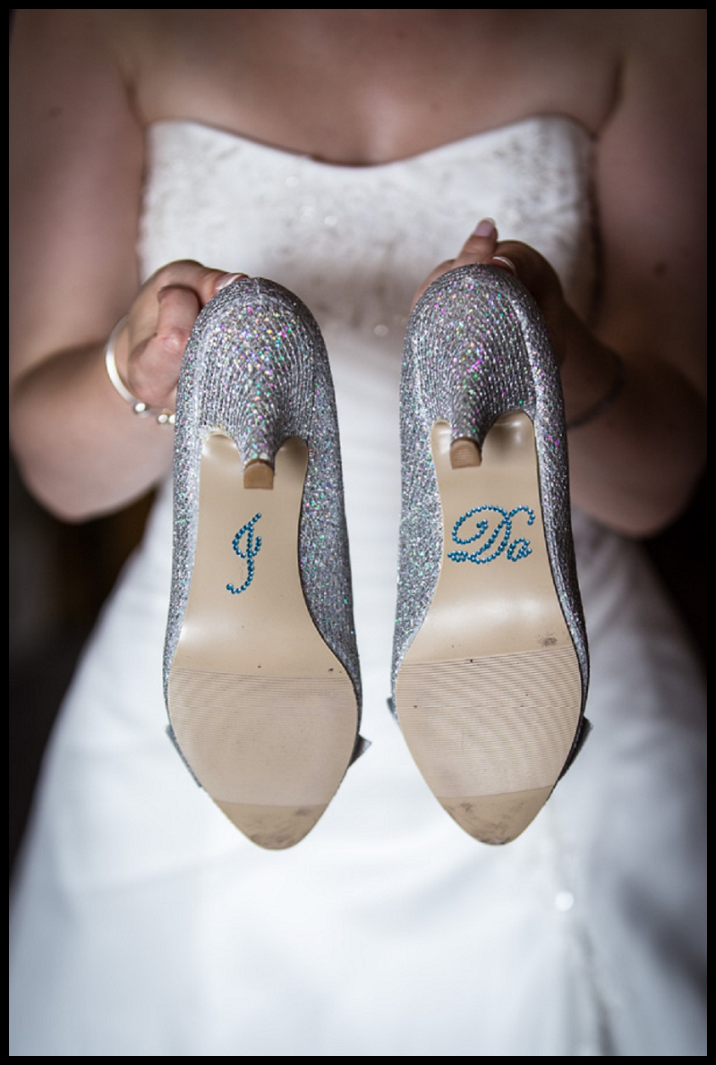 A-bride-in-a-white-dress-holding-her-wedding-shoes-with-the-words-I-DO-on-the-soles.jpg