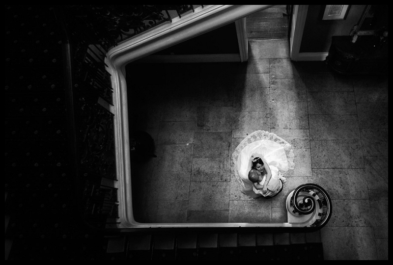 Timeless, romantic black and white image of bride and groom kissing, taken from above on stairs at Addington Palace.jpg