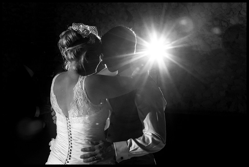 beautiful wedding photography of bride and groom dancing at the granary estates. With flashburst in background