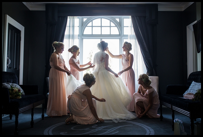 Bridesmaids adjusting brides dress at Paddocks House in front of window
