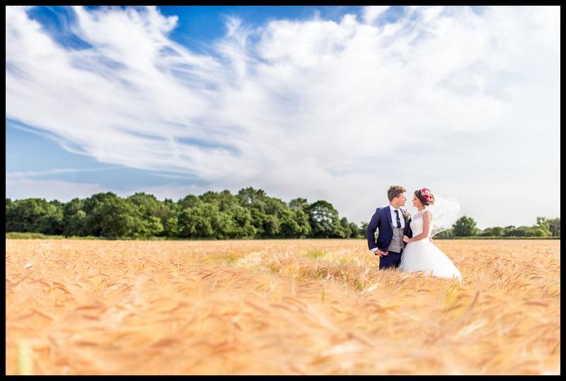 bride and groom in corn field at granary barn