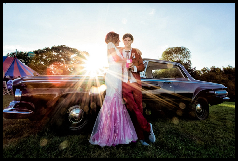 Vintage carnival themed wedding photo of dodge wedding car with bride and groom