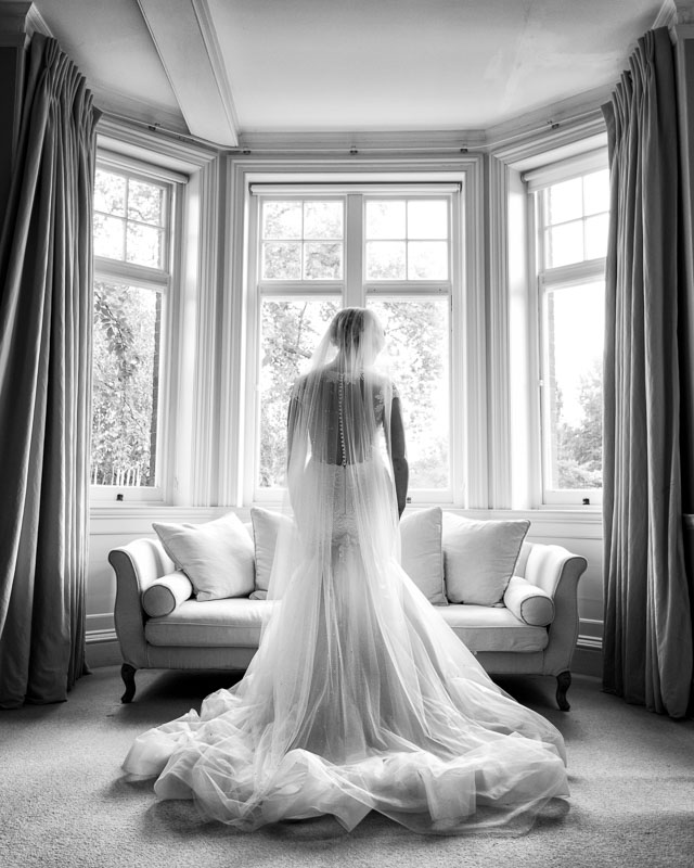 Black and white portrait of bride in beautiful flowing dress in front of window at Chippenham Park in Cambridgeshire