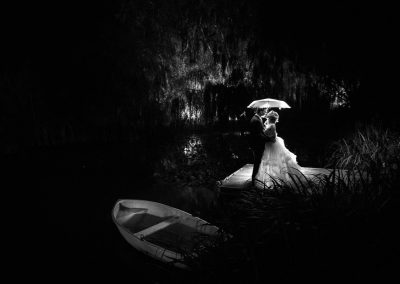 Bride and Groom by lake at night with umbrella at Norfolk Wedding