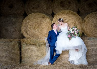 Bride and Groom sitting on hay bales