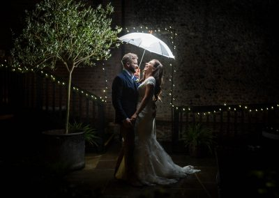 Bride and Groom with Umbrella at Granary Barns