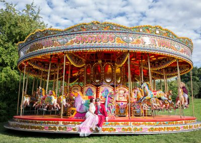 Alternative Bride and groom sitting on fairground carousel