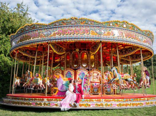 Alternative Bride and groom sitting on fairground carousel