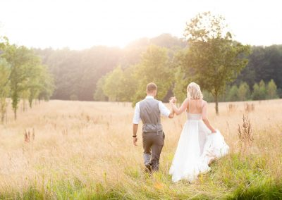 Chaucer Barn Wedding. Couple walking in field