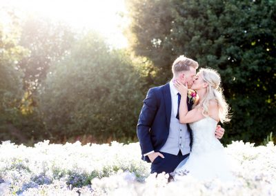 bride and groom kissing in flied at Houchins Wedding Venue