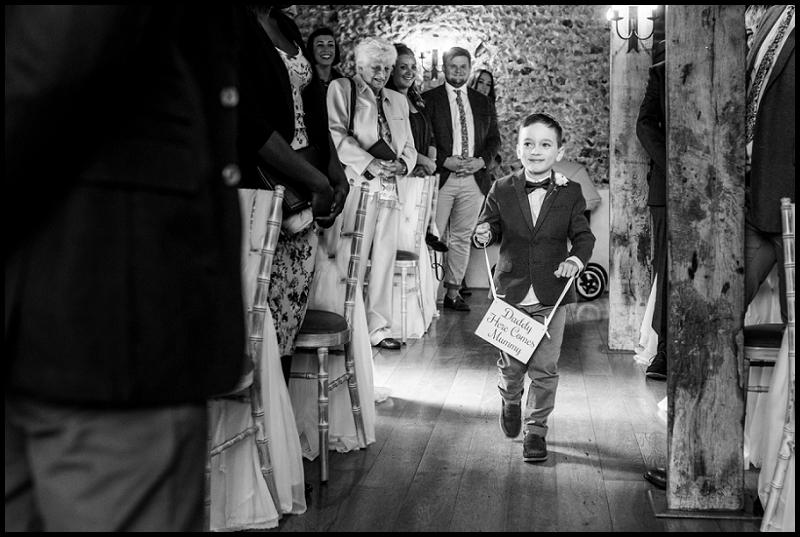 Page Boy walking down aisle at Granary Estates Flint Barn