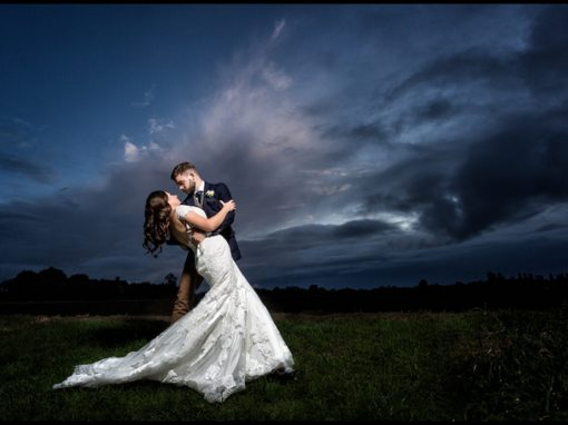 Beautiful portrait of groom dipping bride at the Granary Estates with dramatic sky