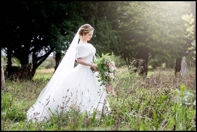 Bride holding bouquet in church yard