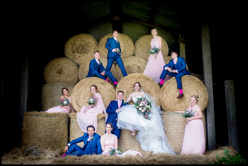 Bridal party with bride and groom on hay bales in Norfolk country barn pub wedding