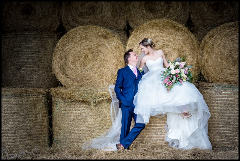 Bride and groom kissing in Norfolk hay barn