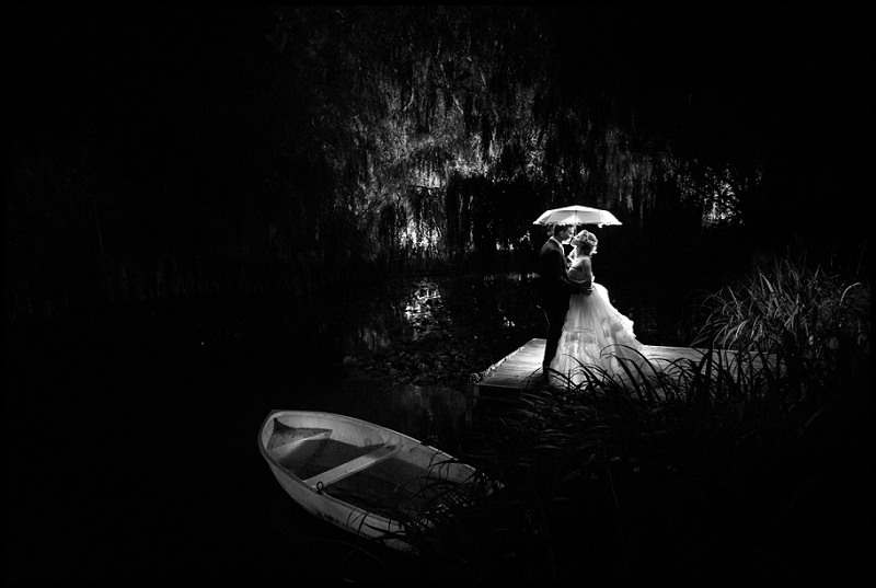 bride and grrom by lake with umbrella and boat