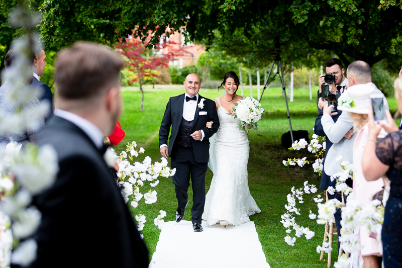 Father escorting Bride down aisle at outdoor ceremony location