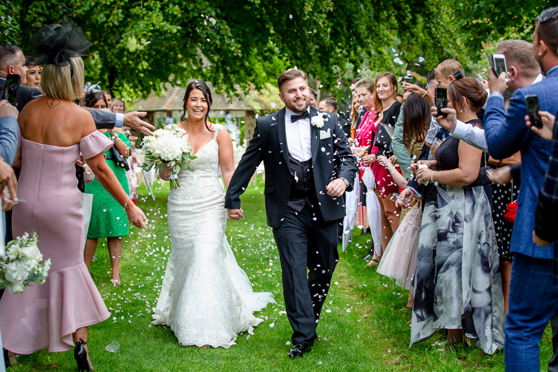 Couple walking down aisle with confetti at Chippenham Park wedding outdoor ceremony