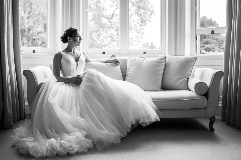 Bride sitting on a sofa in front of a window