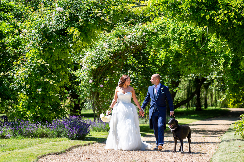 Bride, groom and dog walking along path at Chippenham Park Wedding Venue