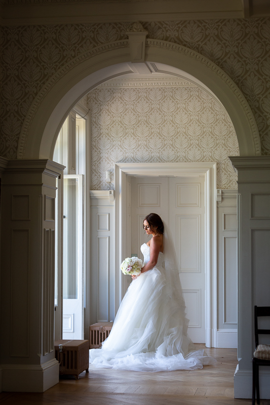 Bride standing near doorway of Chippenham Paerk Wedding Venue