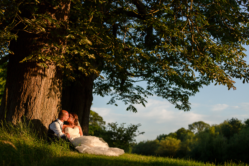 Bride and groom relaxing under tree during Chippenham Park Wedding
