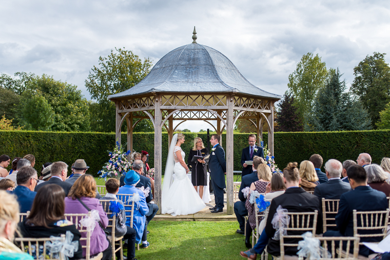 Chippenham Park wedding ceremony outside house under pergola