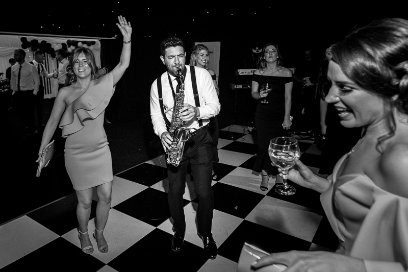 Best man on dancefloor with wedding saxaphone