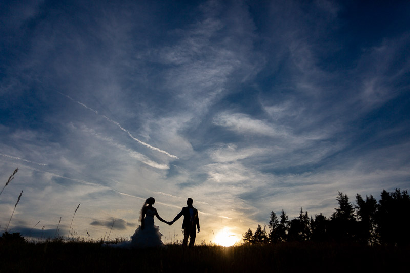 Silhouette of bride and groom walking across sunset
