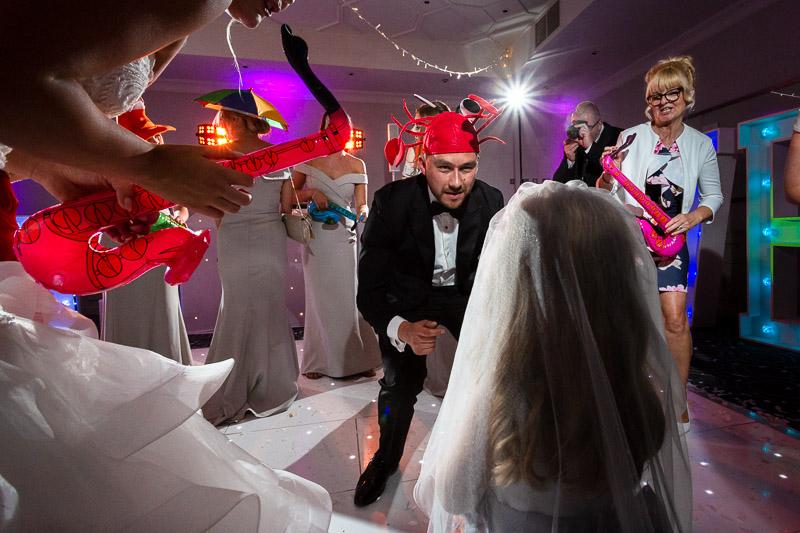 groom wearing lobster hat on dance floor having fun