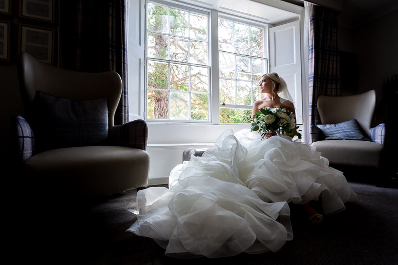 Bride sitting near window and holding flowers at De Vere Wotton House Wedding Venue