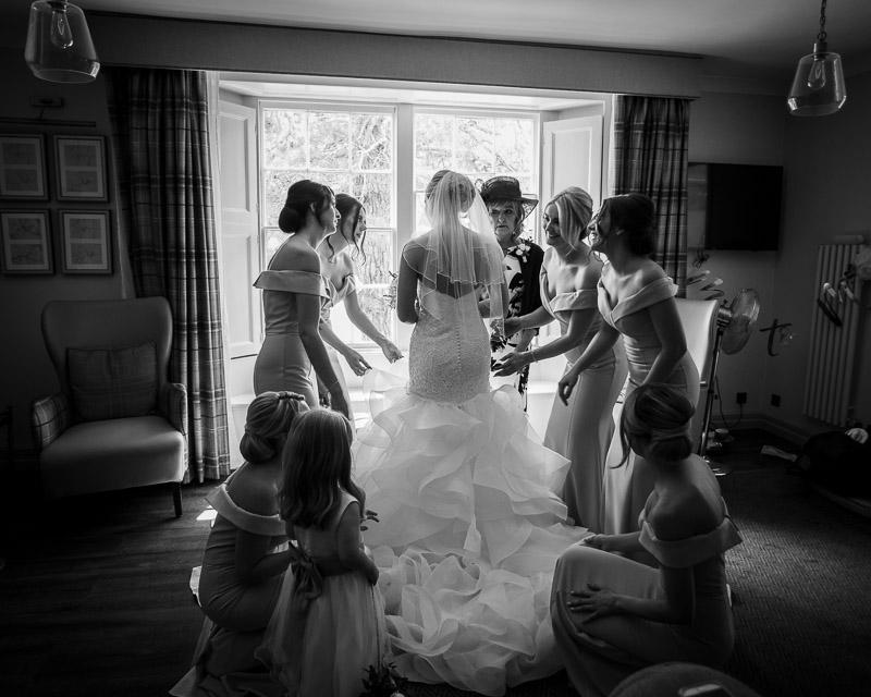 Bridesmaids adjusting brides dress