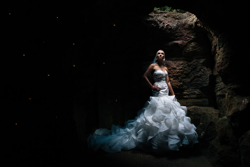 Bride in stunning dress posed in cave at De Vere Wotton House