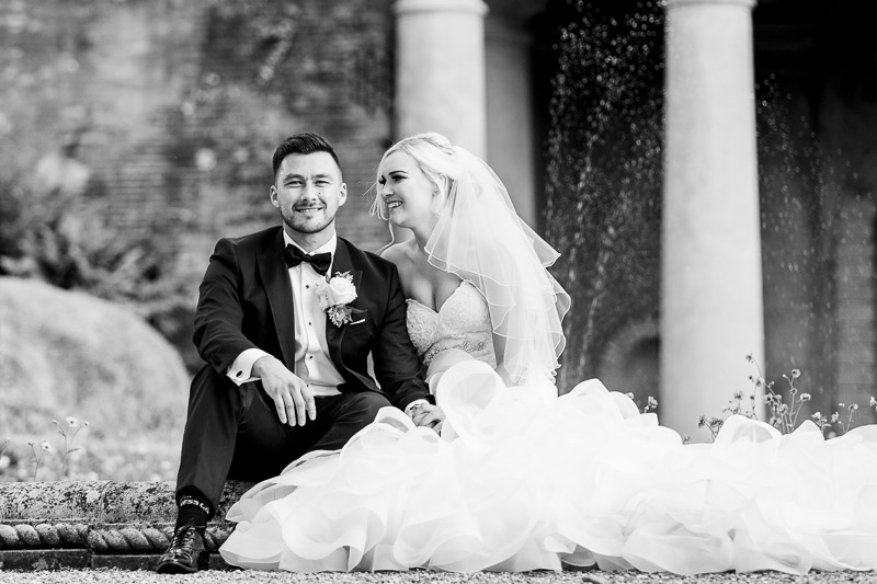 Bride and Groom sitting by fountain