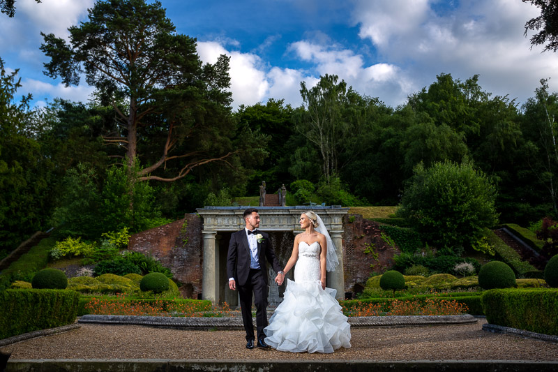 Bride and groom walking hand in hand in gardens at De Vere Wotton House