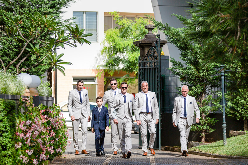 Groomsmen walking in to grounds of Madeira Wedding venue