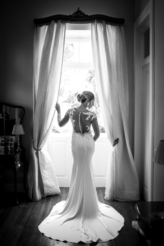 Bride standing by full length window in dress