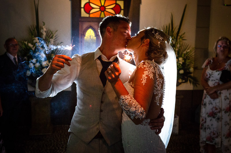 bride and groom holding sparklers and kissing